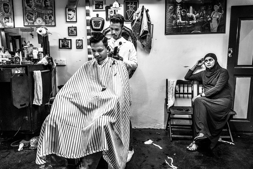 Fitri working on a client at Son & Dad Barbers in George Town, Penang, Malaysia, while his wife waits patiently.