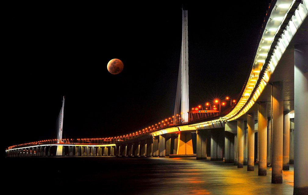 A rising red moon watching over the bridge across the bay in Shenzhen city, China